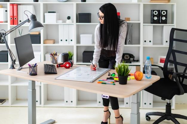 Una joven se encuentra cerca del escritorio de una computadora y dibuja un marcador en una pizarra magnética.