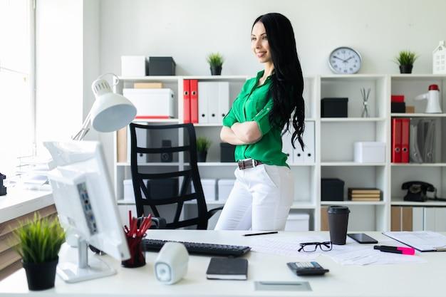 Una joven se encuentra cerca de un escritorio de oficina