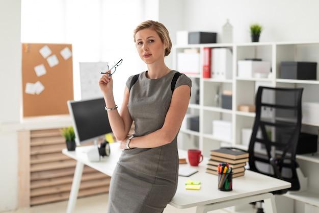 Una joven se encuentra cerca de una mesa en la oficina y tiene gafas en la mano.