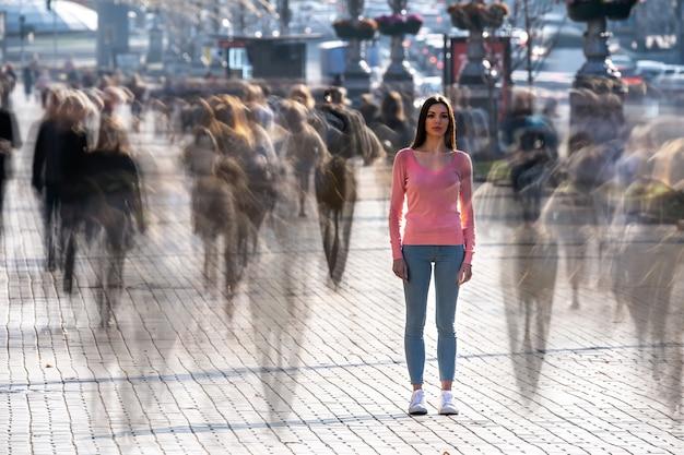 La joven se encuentra en medio de una calle concurrida.