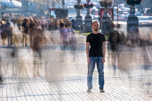 El joven se encuentra en medio de una calle llena de gente.