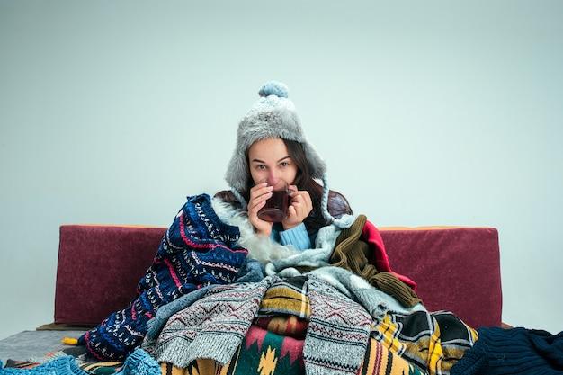 La joven enferma con chimenea sentada en el sofá en casa o estudio cubierto con ropa de abrigo tejida. enfermedad, influenza, concepto de dolor. relajación en casa. conceptos sanitarios.