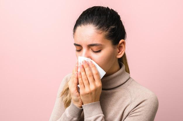 Joven enferma con mosca o virus estornudando y tosiendo con una máscara o servilleta que parece muy desesperada