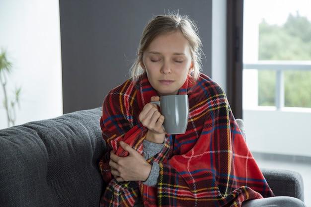 Joven enferma con los ojos cerrados sosteniendo la copa en la mano, con fiebre.