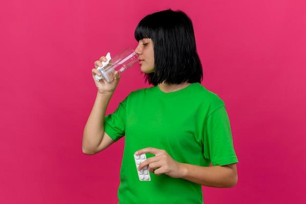 Joven enferma sosteniendo el paquete de tabletas, servilleta y vaso de agua potable aislado en la pared rosa con espacio de copia