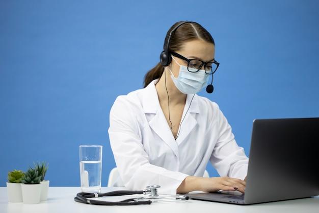 Joven enfermera en bata médica, máscara y auriculares ofrece consulta en línea