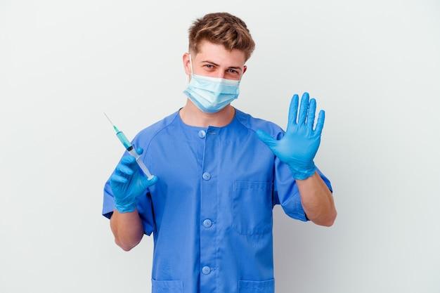 Joven enfermera caucásica preparada para dar una vacuna aislada en la pared blanca sonriendo alegre mostrando el número cinco con los dedos