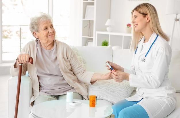 Joven enfermera examinando a anciana con glucómetro en casa