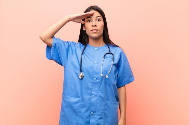 Joven enfermera latina saludando con un saludo militar en un acto de honor y patriotismo, mostrando respeto contra la pared rosa