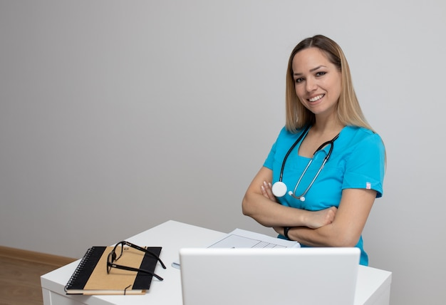 Joven enfermera linda en ropa azul con un estetoscopio