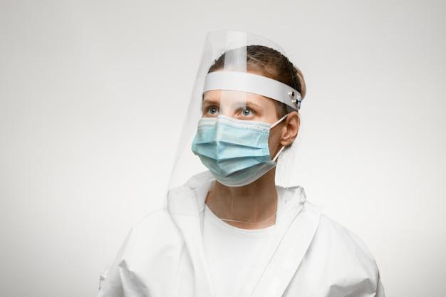 Joven enfermera en máscara médica y escudo protector en la cabeza mira hacia otro lado.