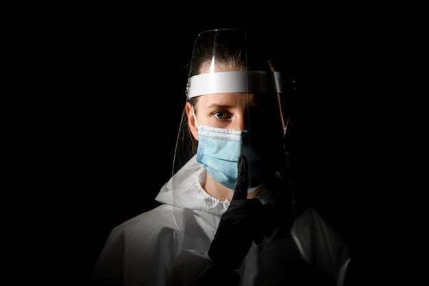 Joven enfermera en máscara médica y escudo protector muestra gesto de silencio.
