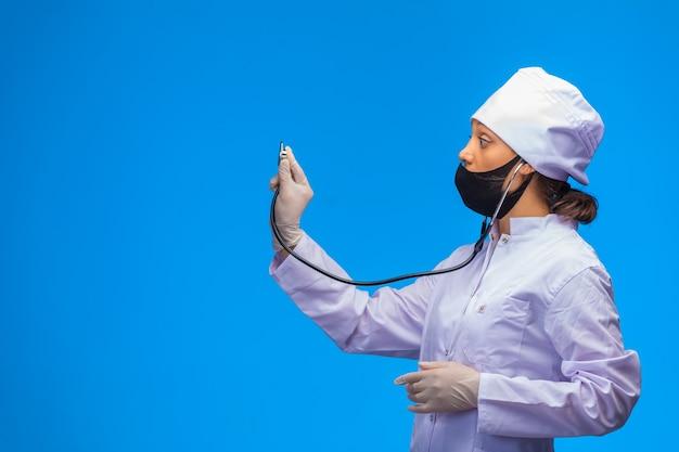 Joven enfermera en mascarilla negra comprueba al paciente con estetoscopio sobre fondo azul.