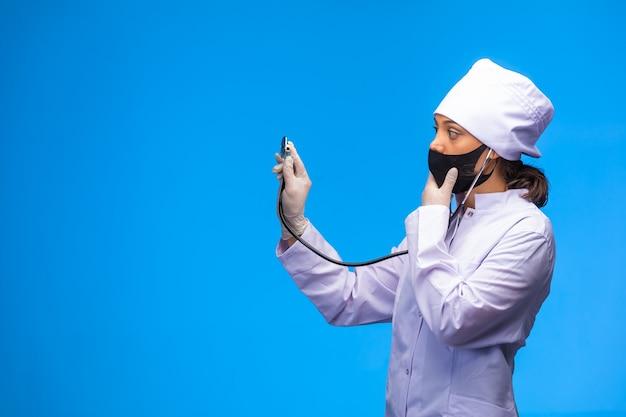 Joven enfermera en mascarilla negra comprueba al paciente con estetoscopio.