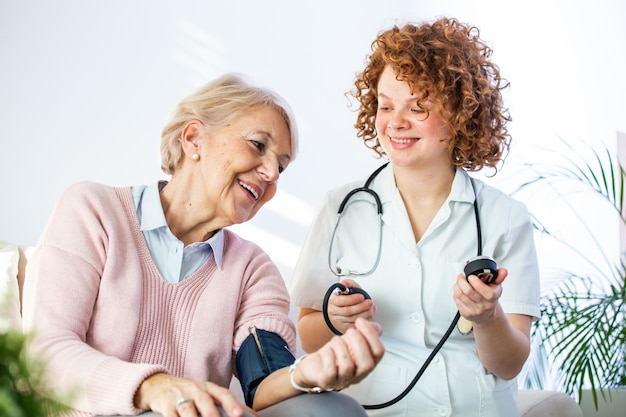 Joven enfermera medir la presión sanguínea de una anciana en casa.