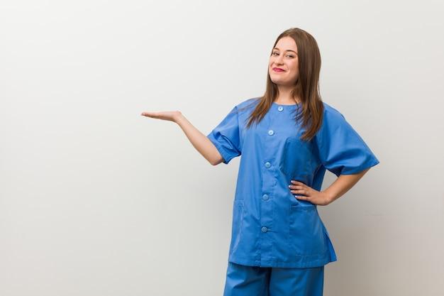 Joven enfermera mujer contra una pared blanca que muestra una copia en una palma y sosteniendo otra mano en la cintura.