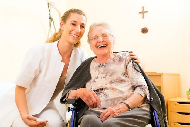 Joven enfermera y mujer senior en hogar de ancianos