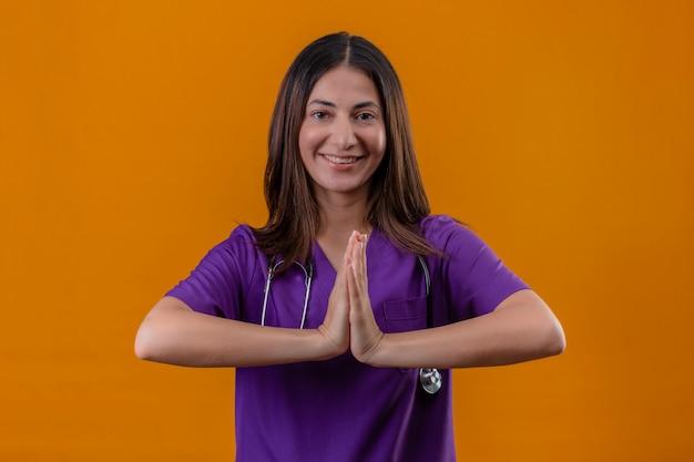 Joven enfermera vestida con uniforme y con estetoscopio tomados de la mano en oración namaste gesto sintiéndose agradecido y feliz