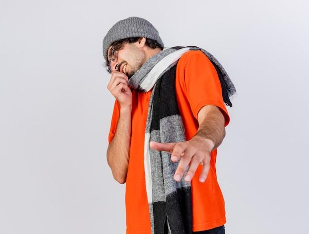 Joven enfermo caucásico molesto con gafas, gorro de invierno y bufanda mirando al lado estirando la mano hacia la cámara manteniendo otra cerca de la boca aislada sobre fondo blanco con espacio de copia