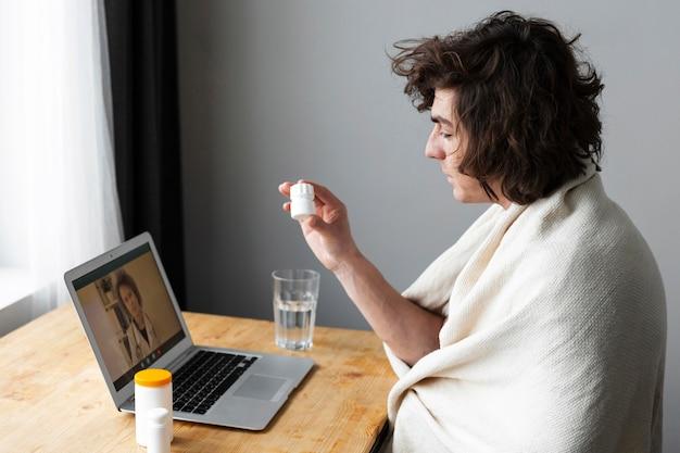 Joven enfermo hablando con su médico en línea