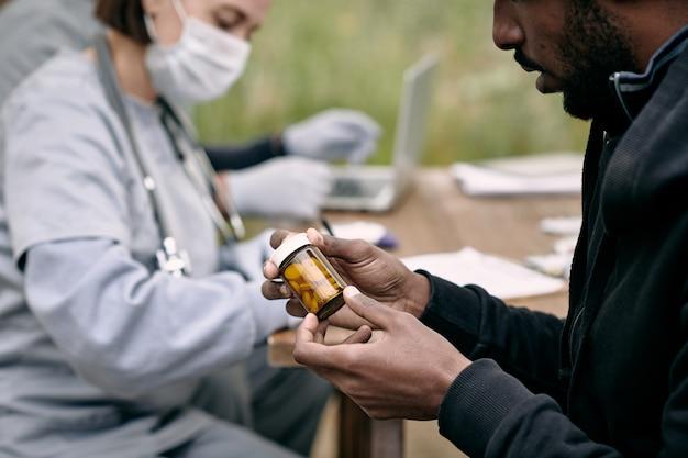 Joven enfermo sosteniendo la botella con pastillas recetadas por el médico