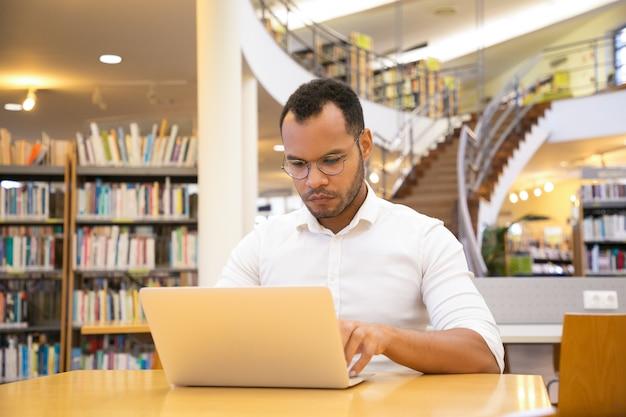 Joven enfocado escribiendo en la computadora portátil en la biblioteca pública