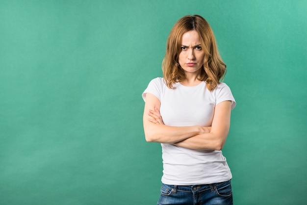 Una joven enojada con los brazos cruzados contra el fondo verde