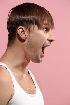 El joven enojado emocional gritando en espacio de estudio rosa