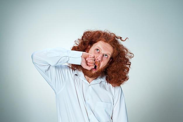 El joven enojado con largo cabello rojo golpeándose a sí mismo