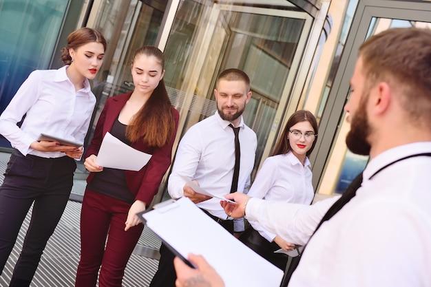 Un joven entrega hojas de papel en blanco a la gente. interrogatorio. encuesta de opinión