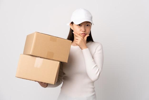 Joven entrega mujer china sobre blanco aislado pensando en una idea