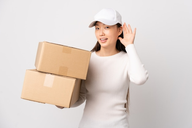Joven entrega mujer china sobre pared blanca aislada escuchando algo