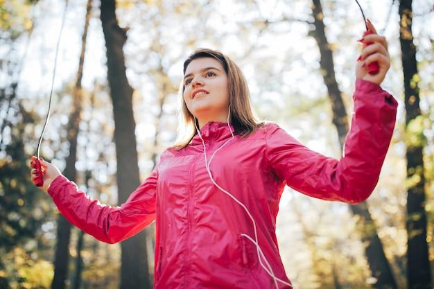 Joven entrena y escucha música al aire libre y salta sobre una cuerda