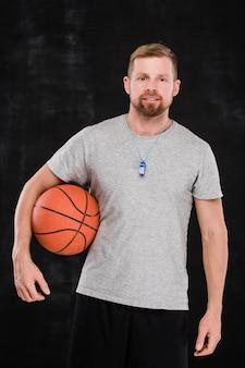 Joven entrenador de baloncesto profesional con bola de pie delante de la cámara contra el fondo negro