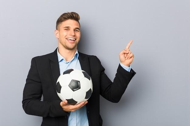 Joven entrenador de fútbol sonriendo alegremente señalando con el dedo lejos.