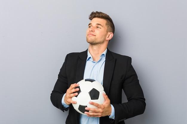 Joven entrenador de fútbol sonriendo confiados con los brazos cruzados.
