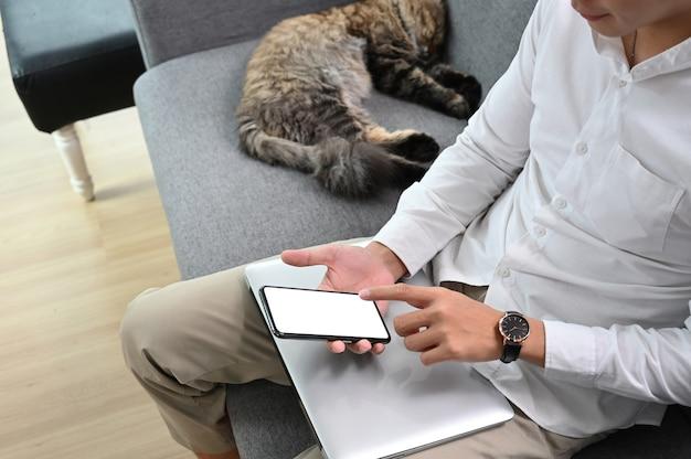 Joven está enviando mensajes de texto en el teléfono inteligente mientras está sentado en el sofá en casa
