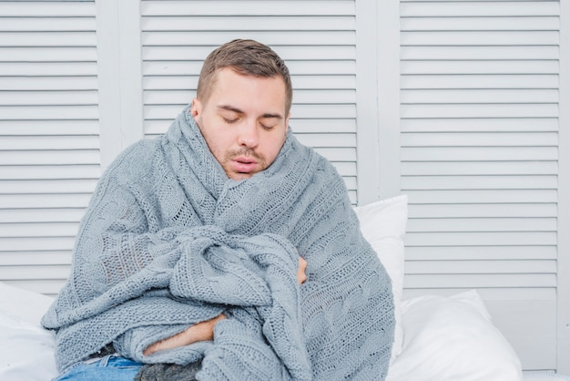 Joven envuelto en una cálida bufanda temblando de frío