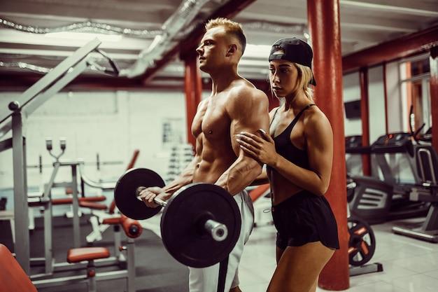 Joven y un equipo de mujer entrenando con pesas