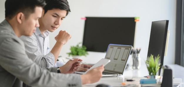 Joven equipo profesional de desarrolladores web ux trabajando en su proyecto de plantilla de teléfono inteligente