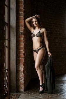 Una joven esbelta se encuentra en ropa interior negra junto a la ventana