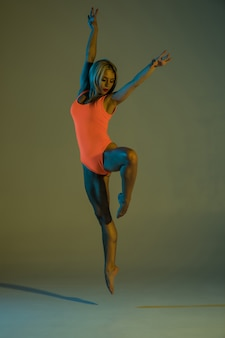 Joven esbelta gimnasia haciendo acrobacias
