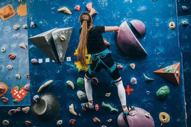 Joven escalando un muro de escalada alto, interior y artificial