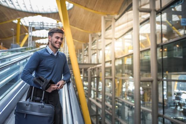 Joven en la escalera mecánica en el aeropuerto con su equipaje sonriendo