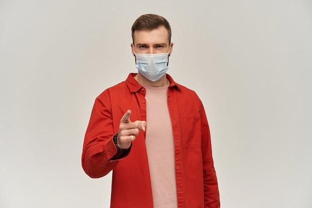 Joven escéptico con barba en camisa roja y máscara higiénica para evitar infecciones apuntando hacia el frente o hacia usted con el dedo sobre la pared blanca