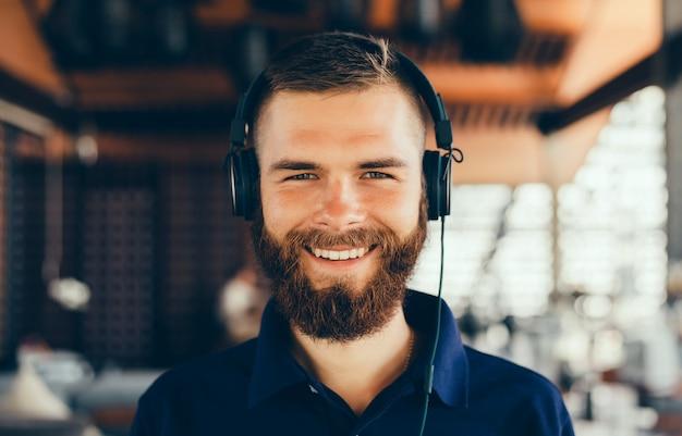 Joven escucha música en auriculares, usando teléfono inteligente, retrato de hipster al aire libre