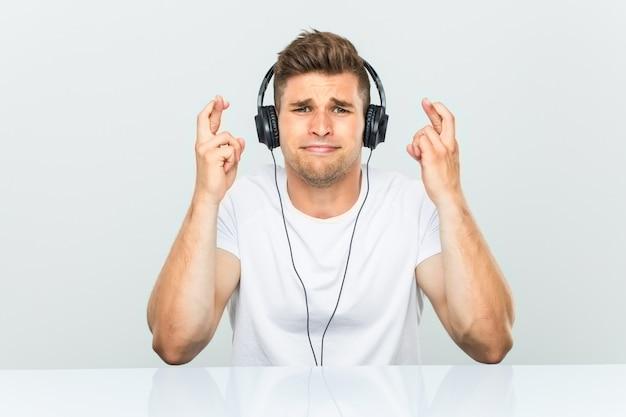 Joven escuchando música con auriculares cruzando los dedos para tener suerte