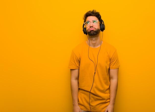 Joven escuchando música cansada y aburrida.