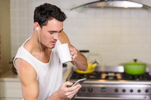 Joven escuchando música en casa en la cocina