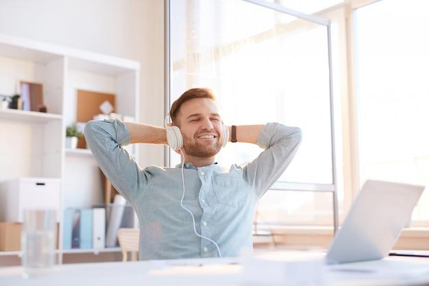 Joven escuchando música en el lugar de trabajo